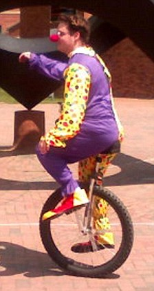 Clown on a unicycle tests mobile phone users
